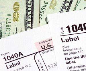 1040 tax form over 20 dollar bills © Fotolia.com
