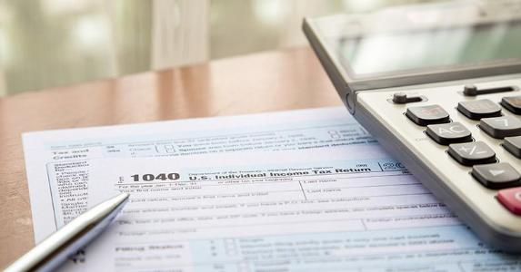 Tax form 1040, a pen and a calculator © vinnstock/Shutterstock.com