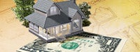 A small house sitting on a large $1 bill with house plans in the background and a couple small green trees