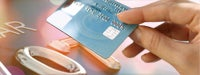 Credit card guide: Woman&#39s hand holding blue credit card on peach background