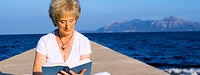 Retirement Guide: Senior woman sitting on dock, reading a book