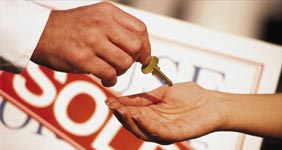 Real estate agent handing off house keys to homebuyer