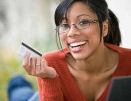 Young woman smiling and holding a credit card