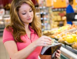 Woman sorting coupons in grocery shop