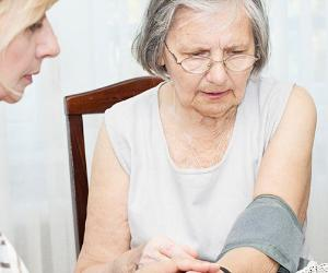Adult daughter checking blood pressure of elderly mother
