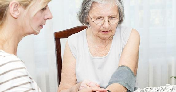 Adult daughter checking blood pressure of elderly mother | iStock.com/BakiBG
