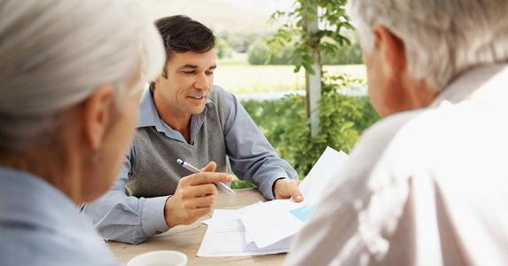 Adult son showing paperwork to elderly parents