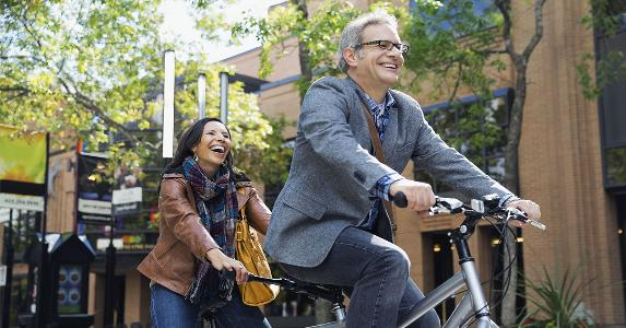 Couple riding a tandem bicycle | Hero Images/Getty Images