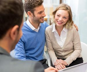 Adviser holding tablet computer, talking to clients © iStock
