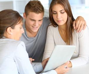 Adviser showing data on tablet to couple © Goodluz/Shutterstock.com