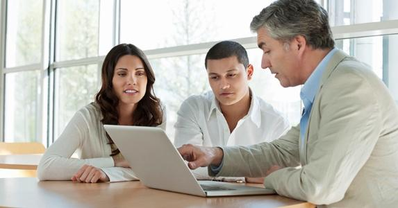 Adviser showing laptop's screen to client couple | iStock.com/Johnny Greig