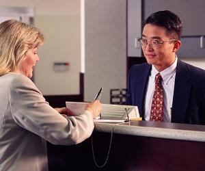 Bank teller with customer signing checkbook © Steve Smith/Shutterstock.com