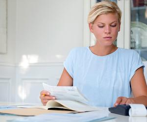 Blond woman at table calculating bills