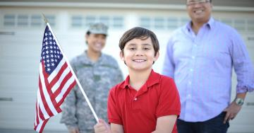 Boy holding the American flag | Veterans United