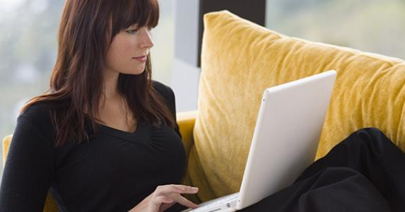 Brunette woman in black top using laptop at home © Darren Baker - Fotolia.com