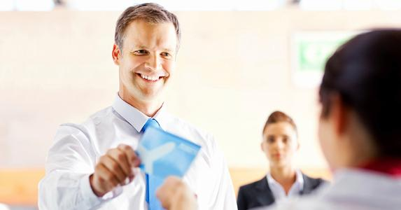 Businessman handing out plane ticket to ground attendant