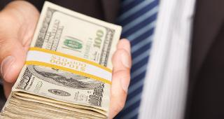 Businessman handing over stack of hundred dollar bills © Andy Dean Photography/Shutterstock.com