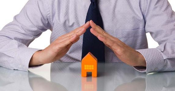 Businessman holding hands over toy house   iStock.com/hjalmeida