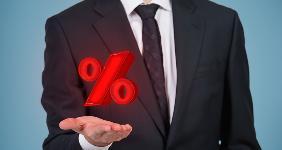 Businessman holding percentage mark © Ismagilov/Shutterstock.com