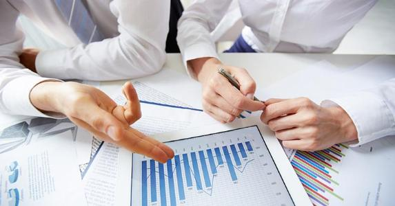 Businessmen discussing column graphs | iStock.com/shironosov