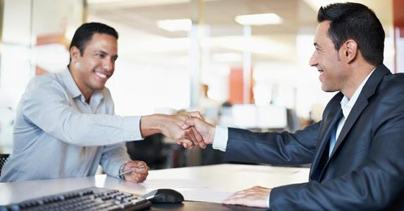 Businessmen shaking hands in an office © iStock