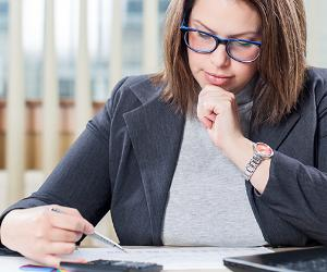 Businesswoman using calculator in office