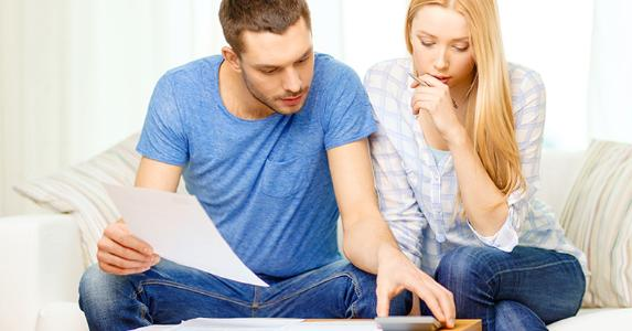 Busy couple with papers and calculator at home © Syda Productions/Shutterstock.com