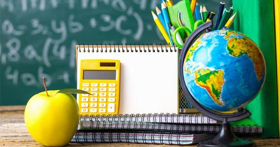 Calculator, notebooks, pens and other school supplies on a desk © Zadorozhna Natalia/Shutterstock.com