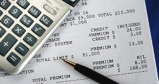 Calculator on insurance bill © JohnKwan/Shutterstock.com