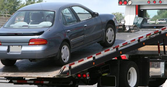 Car being lifted onto tow truck bed