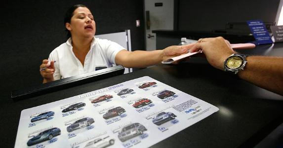 Car rental employee handing packet to customer | Brian Vander Brug/Los Angeles Times/Getty Images