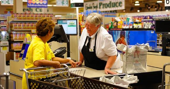 Cashier laughing with customer | Joe Amon/Getty Images