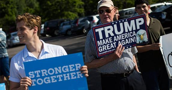 Hillary Clinton and Donald Trump supporters standing side-by-side holding signs | Boston Globe/Getty Images