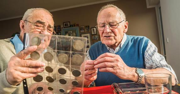 Coin collectors examining coins | Westend61/Getty Images