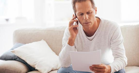 Concerned man calling adviser, looking at papers © iStock