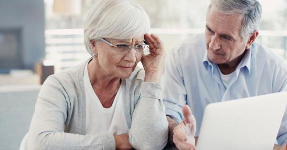Senior couple stressed, concerned over bills | iStock.com/Squaredpixels