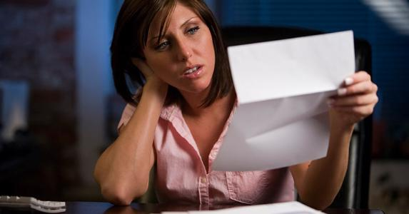 Confused woman reading paperwork © iStock
