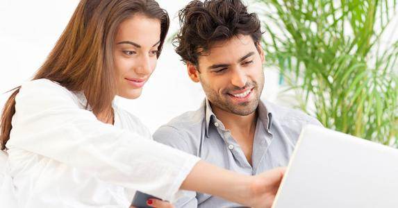 Couple at home using laptop © iStock