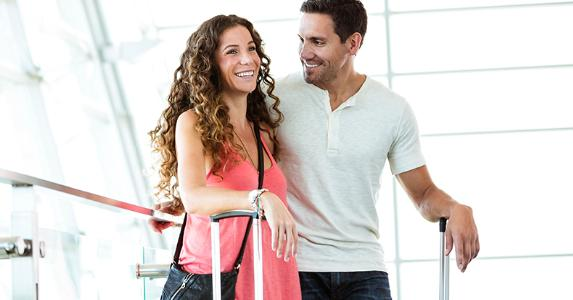 Couple in airport, standing and laughing