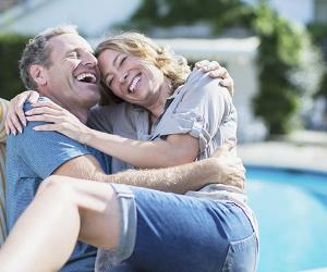 Couple laughing by the poolside | Paul Bradbury/Shutterstock.com