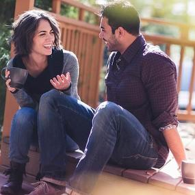 Couple laughing while sitting on front porch | Chad Springer/Image Source/Getty Images