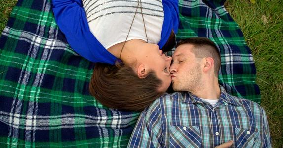 Couple laying on blanket outside, man kissing woman's forehead | Annie Otzen/Moment/Getty Images