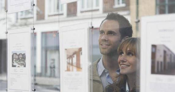 Couple looking at real estate listing in window | bikeriderlondon/Shutterstock.com