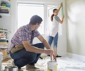 Couple painting kitchen | Hero Images/Getty Images