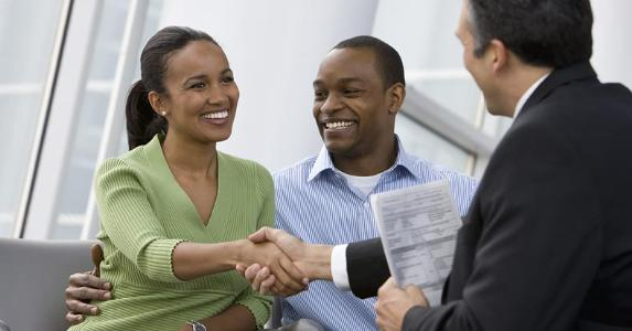 Couple shaking hands with financial adviser   Blend Images – Ariel Skelley/Brand X Pictures/Getty Images