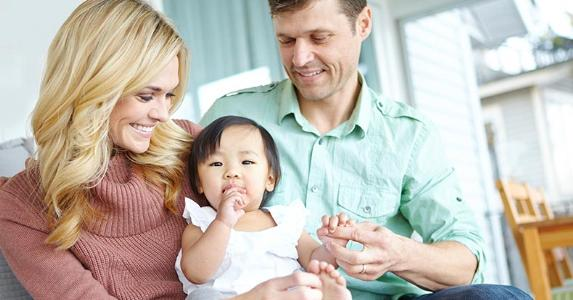 Couple with adopted baby daughter | iStock.com/gradyreese