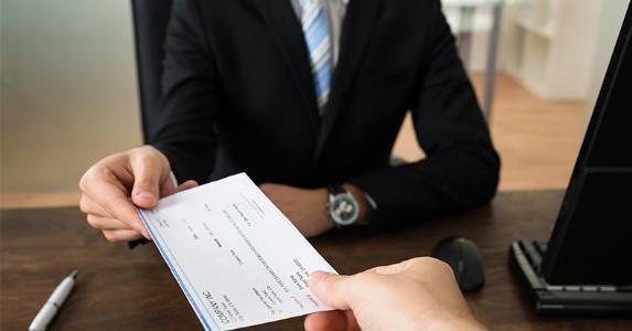 Customer handing over a cashier's check © Andrey_Popov/Shutterstock.com