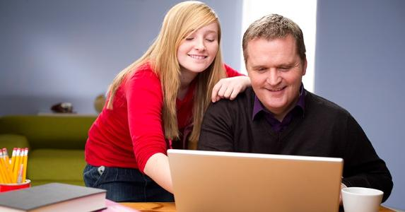 Dad and teenage daughter browsing laptop at home © iStock