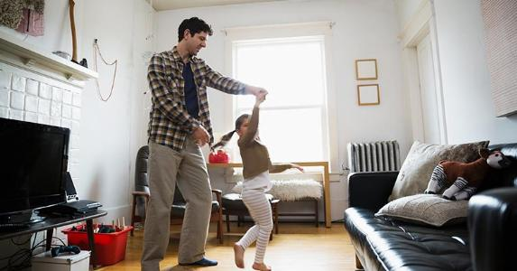 Dad and young daughter dancing in living room | Hero Images/Getty Images