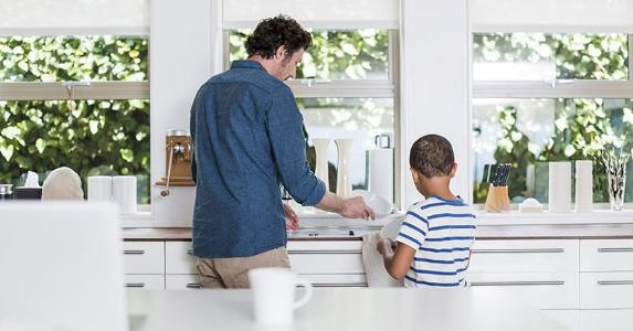 Dad and young son drying dishes in the kitchen | Portra Images/DigitalVision/Getty Images